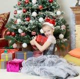 Bambina che si siede vicino all'albero di Natale con un grande regalo Immagine Stock Libera da Diritti