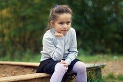 Bambina che si siede vicino alla sabbiera Fotografie Stock