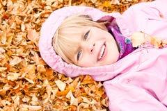 Bambina che si trova in fogli di autunno Fotografia Stock Libera da Diritti