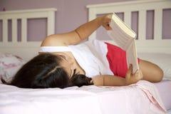 Bambina che si trova a letto stanza fotografia stock libera da diritti