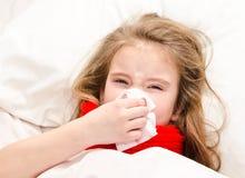 Bambina che si trova nel letto e che soffia il suo naso Immagini Stock