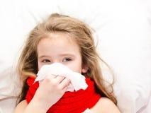 Bambina che si trova nel letto e che soffia il suo naso Immagine Stock