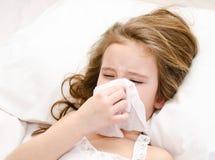 Bambina che si trova nel letto e che soffia il suo naso Fotografia Stock