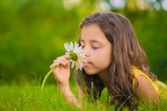 Bambina che si trova nell'erba e negli odori un fiore Immagine Stock Libera da Diritti