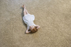 Bambina che si trova sul tappeto a casa Fotografia Stock Libera da Diritti