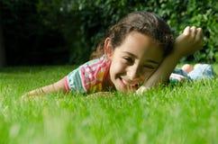 Bambina che si trova sull'erba e che esamina macchina fotografica Fotografia Stock Libera da Diritti