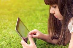 Bambina che si trova sull'erba e sui tocchi lo schermo una compressa Fotografie Stock Libere da Diritti