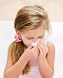 Bambina che soffia il suo naso in un grande sforzo Fotografie Stock Libere da Diritti