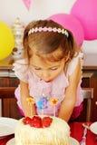 Bambina che soffia le candele fotografia stock