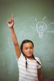 Bambina che solleva mano in aula Fotografie Stock