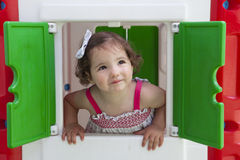 Bambina che sorride attraverso la finestra della casetta per giocare dei bambini Fotografia Stock Libera da Diritti