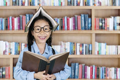 Bambina che sorride con il libro sopra la sua testa Fotografie Stock