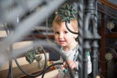 Bambina che sorride e che guarda tramite un recinto del metallo Fotografia Stock