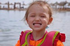 Bambina che sorride sulla spiaggia immagini stock