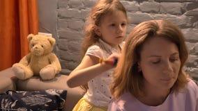 Bambina che spazzola i suoi capelli del ` s della madre con la spazzola per i capelli, fondo moderno del salone, concetto 'nucleo stock footage