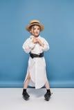 Bambina che sta in cappello bianco di paglia e della camicia mentre distogliendo lo sguardo Immagine Stock