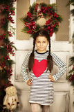 Bambina che sta vicino alla porta con la ghirlanda di natale Fotografia Stock Libera da Diritti