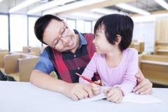 Bambina che studia con l'insegnante maschio nella classe Fotografia Stock Libera da Diritti