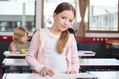 Bambina che studia mentre stando allo scrittorio Fotografia Stock