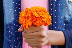 Bambina che tiene il mazzo giallo del fiore del tagete immagine stock
