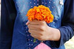 Bambina che tiene il mazzo giallo del fiore del tagete fotografia stock