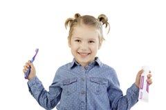 Bambina che tiene il suoi spazzolino da denti e dentifricio in pasta Fotografie Stock