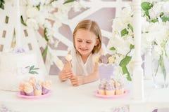 Bambina che tiene le lecca-lecca dolci variopinte nella barra di caramella Immagini Stock Libere da Diritti