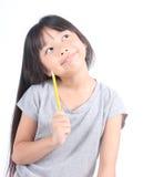 Bambina che tiene matita gialla, pensante immagini stock