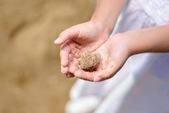 Bambina che tiene sabbia di mare immagine stock