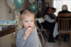 Bambina che tiene un bigné con glassa sul fronte alla nascita della famiglia immagini stock libere da diritti