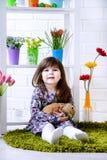 Bambina che tiene un coniglio lanuginoso con i fiori intorno Fotografia Stock