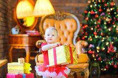Bambina che tiene un regalo da un nastro rosso immagini stock libere da diritti
