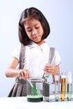 Bambina che tiene una provetta con chimica e scienza liquide dello scienziato fotografia stock