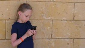Bambina che usando telefono e condizione vicino alla parete di pietra beige archivi video