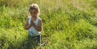 Bambina chiusa lei occhi che pregano al tramonto Le mani hanno piegato nel concetto di preghiera per fede, spiritualità e la reli fotografie stock