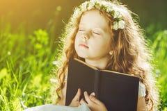 Bambina chiusa lei occhi, pregando, sognando o leggendo un libro Immagine Stock