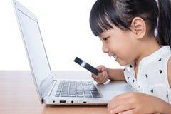 Bambina cinese asiatica che esamina computer portatile tramite la lente Immagini Stock