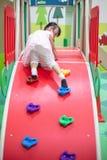 Bambina cinese asiatica che gioca alla mini parete di arrampicata fotografie stock libere da diritti