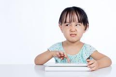 Bambina cinese asiatica che gioca con il computer della compressa immagini stock