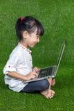 Bambina cinese asiatica che gioca con il computer portatile Immagini Stock