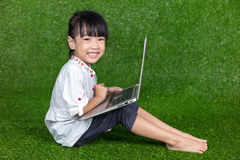 Bambina cinese asiatica che gioca con il computer portatile Fotografia Stock