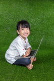 Bambina cinese asiatica che gioca con il computer portatile Immagini Stock Libere da Diritti