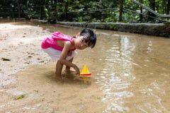 Bambina cinese asiatica che gioca il crogiolo di giocattolo all'insenatura Immagini Stock