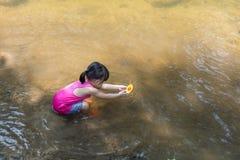 Bambina cinese asiatica che gioca il crogiolo di giocattolo in The Creek Immagini Stock