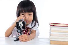 Bambina cinese asiatica che guarda tramite il microscopio Fotografie Stock Libere da Diritti