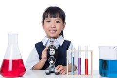 Bambina cinese asiatica che lavora con il microscopio Fotografie Stock Libere da Diritti