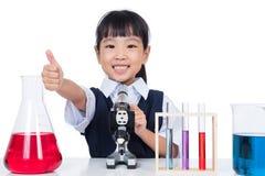 Bambina cinese asiatica che lavora con il microscopio Fotografia Stock