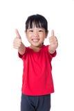 Bambina cinese asiatica che mostra i pollici su Fotografie Stock