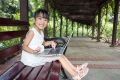 Bambina cinese asiatica che si siede sul banco con il computer portatile Immagine Stock