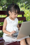 Bambina cinese asiatica che si siede sul banco con il computer portatile Fotografie Stock Libere da Diritti